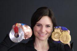 Andrea Henkel Burke mit Medaillen in der Hand _Testimonial kPNI - Akademie